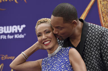 """In this May 21, 2019 file photo, Will Smith, right, kisses Jada Pinkett Smith as they arrive at the premiere of """"Aladdin"""" at the El Capitan Theatre in Los Angeles. (Photo by Chris Pizzello/Invision/AP, File)"""