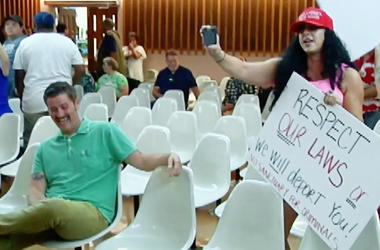"""This photo from video provided by KVOA-TV shows Alex Kack, in the green shirt at left, laughing at a protester during a vote to put a """"sanctuary city"""" initiative on the November ballot during a meeting of the Tucson, Ariz., City Council Tuesday. (KVOA-TV"""
