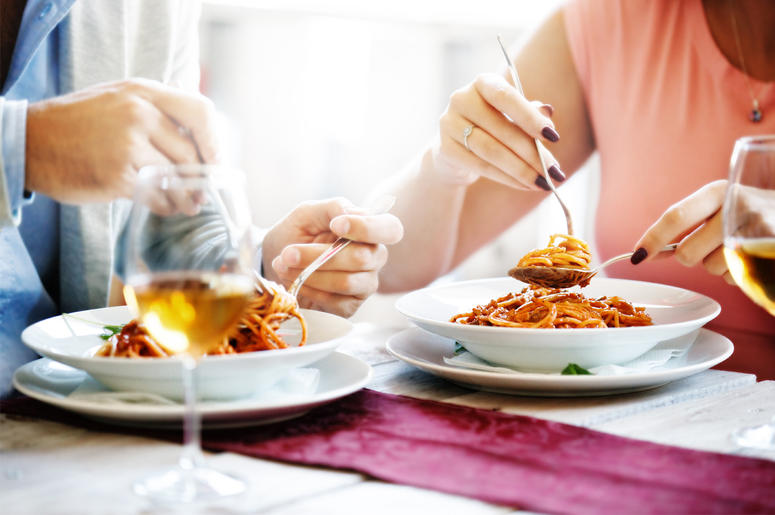 Couple in a restaurant, eating spaghetti. (Photo credit: Getty Images)