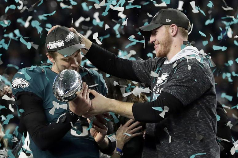 Philadelphia Eagles quarterback Carson Wentz, right, hands the Vincent Lombardi trophy to Nick Foles