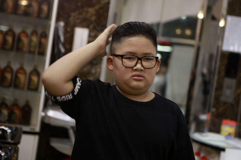 To Gia Huy, 9 checks his hair after having a Kim haircut in Hanoi, Vietnam, on Tuesday, Feb. 19, 2019. U.S. President Donald Trump and North Korean leader Kim Jong Un have become the latest style icons in Hanoi, a week before their second summit is to be