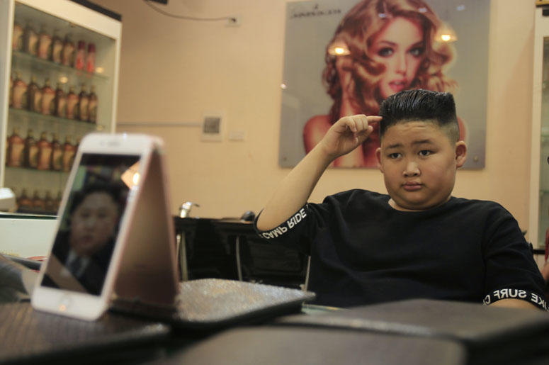 To Gia Huy, 9, checks his hair after having a Kim Jong Un haircut in Hanoi, Vietnam, on Tuesday, Feb. 19, 2019. U.S. President Donald Trump and North Korean leader Kim Jong Un have become the latest style icons in Hanoi, a week before their second summit