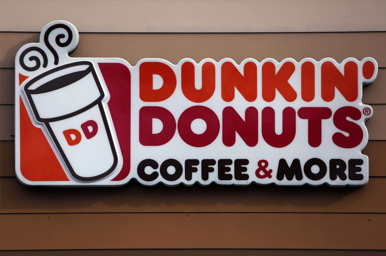 """In this Jan. 22, 2018, file photo shows the Dunkin' Donuts logo on a shop in Mount Lebanon, Pa. Dunkin' is dropping the donuts — from its name, anyway. Doughnuts are still on the menu, but the company is renaming itself """"Dunkin'"""" to reflect its increasing"""