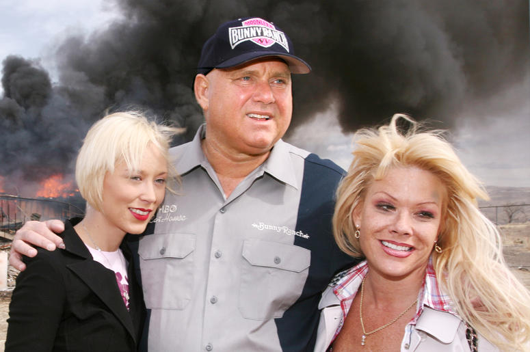 """In this March 25, 2007, file photo, Moonlite Bunnyranch brothel owner Dennis Hof poses with two of his """"working girls"""" Brooke Taylor, left, and a woman working under the name """"Airforce Amy"""", right, as firefighters burn down remains of the former Mustang R"""