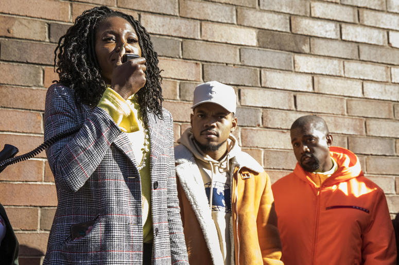 """Chicago mayoral candidate Amara Enyia speaks as Chance the Rapper, center, and Kanye West listen during a """"pull-up"""" rally for Enyia Tuesday, Oct. 23, 2018, in Chicago. (Ashlee Rezin/Chicago Sun-Times via AP)"""
