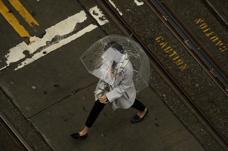 A woman walks in the rain while crossing an intersection in San Francisco, Wednesday, Jan. 16, 2019. A series of storms dropped rain up and down the state and snow in mountain regions this week, but the latest storm could be the strongest that Northern Ca