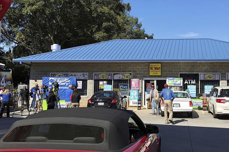 In this Oct. 24, 2018, file photo, media, at left, record people entering the KC Mart in Simpsonville, S.C., after it was announced the winning Mega Millions lottery ticket was purchased at the store. (AP Photo/Jeffrey Collins, File)
