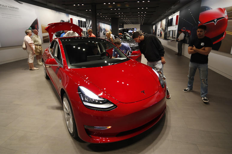 In this July 6, 2018, file photo prospective customers confer with sales associates as a Model 3 sits on display in a Tesla showroom in the Cherry Creek Mall in Denver. (AP Photo/David Zalubowski, File)