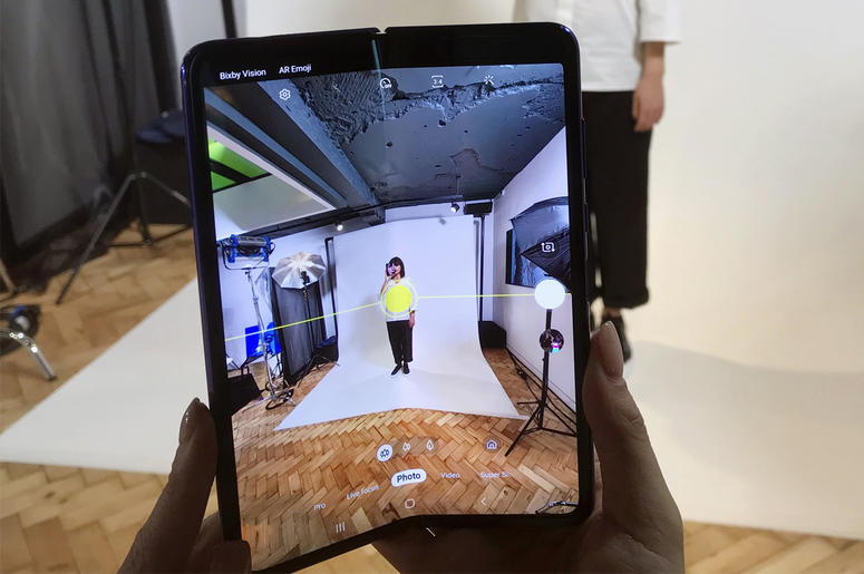 In this April 16, 2019, photo, a model holds a Samsung Galaxy Fold smart phone to her face, during a media preview event in London. (AP Photo/Kelvin Chan)