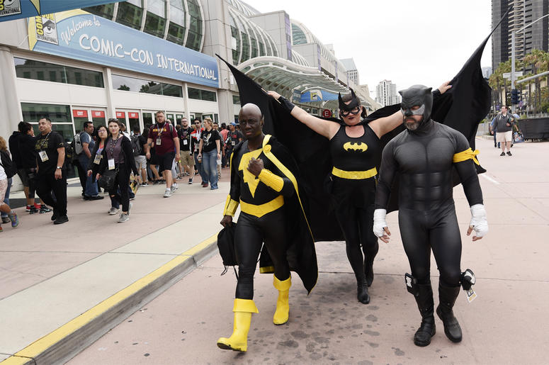 """Jay Acey of New York City, left, dressed as DC Comics character """"Black Adam,"""" Faeren Adams of San Diego, center, dressed as """"Batgirl,"""" and Derek Shackleton of San Diego, dressed as DC Comics character """"Wildcat,"""" walk together outside Preview Night at the"""