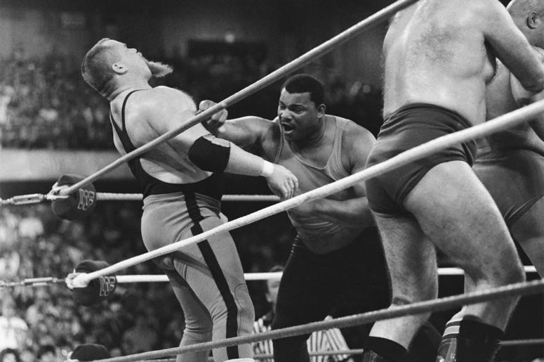 """This April 7, 1986, file photo shows Chicago Bears' William Perry, right, landing a punch on pro wrestler Jim """"The Anvil"""" Neidhart during the """"Over-The-Top-Rope"""" battle royal at Wrestlemania 2 in Rosemont, Ill. Neidhart, who joined with Bret Hart to form"""