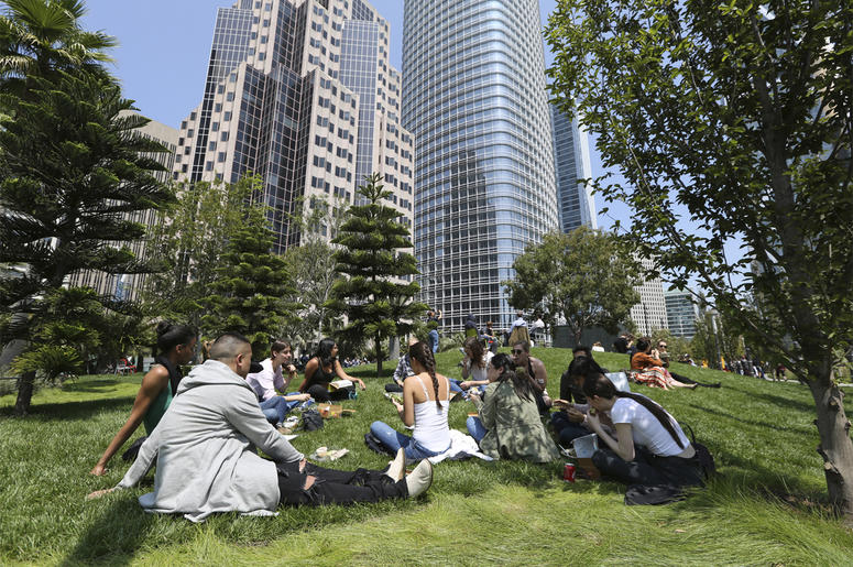 In this photo taken Wednesday, Aug. 15, 2018, employees from marketing company Linqia have a picnic lunch on the rooftop park of the new Transbay Transit Center in San Francisco. The new $2.2 billion center opened earlier this month. (AP Photo/Lorin Eleni