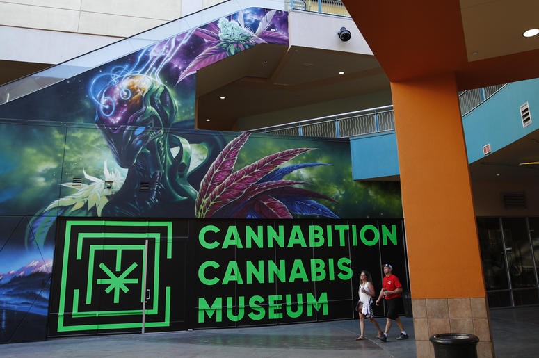 In this Tuesday, Sept. 18, 2018 photo, people walk by the Cannabition cannabis museum in Las Vegas. The museum celebrating all things cannabis with displays that include a glass bong taller than a giraffe and huggable faux marijuana buds is the newest tou