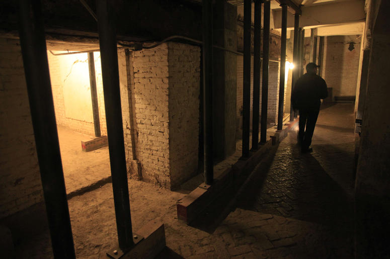 In this July 7, 2011, file photo, Jim Breeden of the Golden Gate National Parks Conservancy, walks through the dungeons below the main cell house during a night tour on Alcatraz Island in San Francisco. (AP Photo/Eric Risberg)
