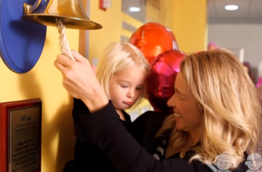 Jenn Hobby and Reese ring the bell