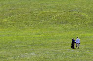 Carol Laura, left, and George Acquaire walk barefoot to a peace sign mowed in the grass at the site of the 1969 Woodstock Music and Arts Fair, Wednesday, July 24, 2019 in Bethel, N.Y. Woodstock will be celebrated on its 50th anniversary, but it won't be y