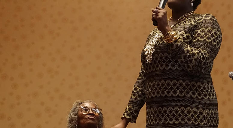 Mrs. Juanita Abernathy is serenaded by Nia Sade' Akinyemi during a recent NAACP awards event