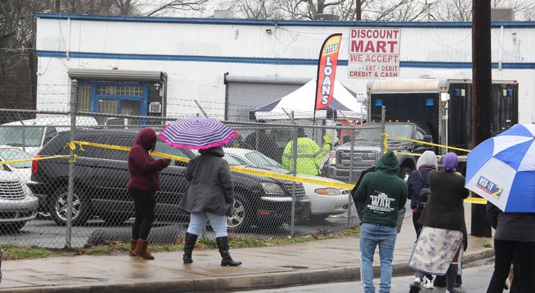 Onlookers gathered outside the Lee Street auto retail shop where 2 men were found dead inside an SUV