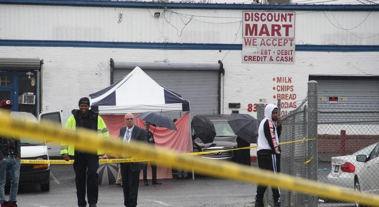 A blue and white tent with red tarp surrounds the SUV in which the bodies of two men were found outside an auto sales shop