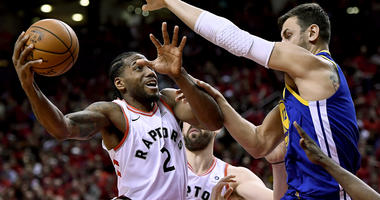 Toronto Raptors forward Kawhi Leonard stretches to keep the ball from Golden State Warriors center Andrew Bogut as he drives to the net during Game 2 of the NBA Finals.