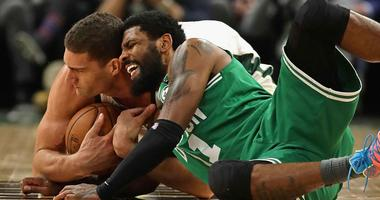 Kyrie Irving of the Boston Celtics fights for a loose ball with the Milwaukee Bucks' Brook Lopez during the second round of the 2019 NBA playoffs.