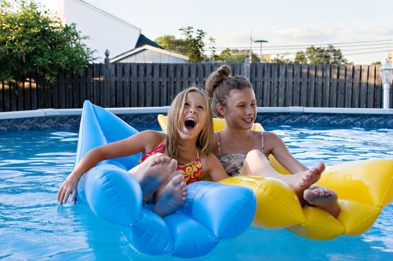 two young children floating in a backyard pool