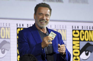 """Arnold Schwarzenegger gets twenty dollars after winning a bet to fellow cast member Diego Boneta at the """"Terminator: Dark Fate"""" panel on day one of Comic-Con International on Thursday, July 18, 2019, in San Diego."""