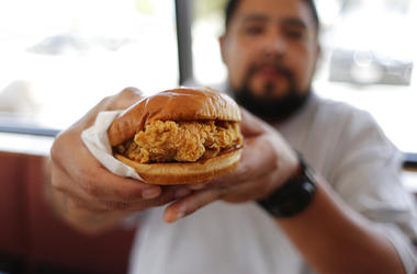 Randy Estrada holds up his chicken sandwiches at a Popeyes