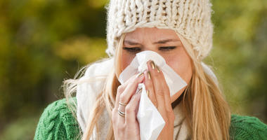 A woman with the flu sneezes into a tissue.
