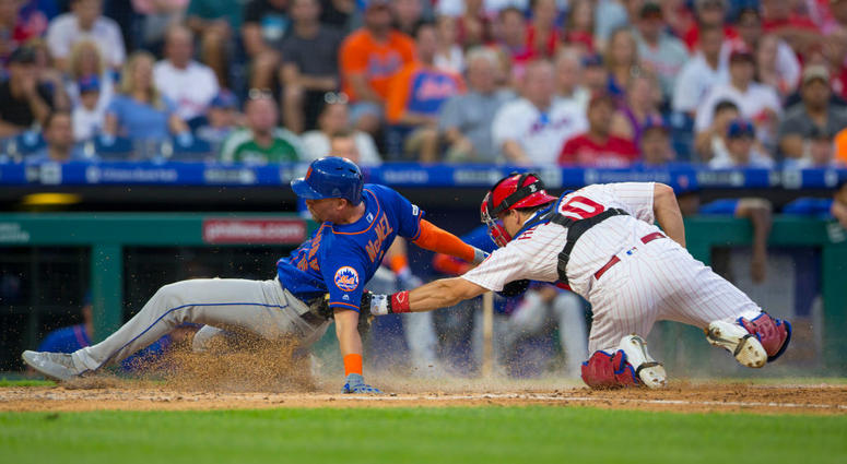 J.T. Realmuto #10 of the Philadelphia Phillies tags out Jeff McNeil #6 of the New York Mets in the top of the fourth inning at Citizens Bank Park on June 25, 2019