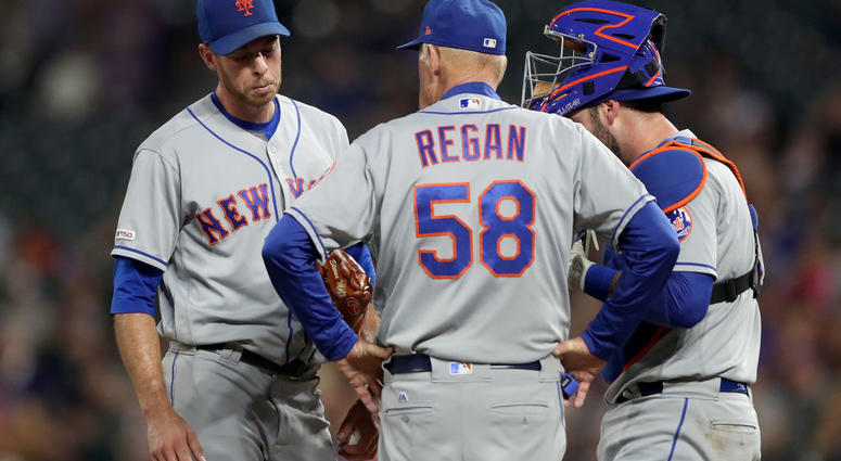 Starting pitcher Steven Matz #32 , pitching coach Phil Regan #58 and catcher Tomas Nido #3 of the New York Mets confer in the fourth inning against the Colorado Rockies at Coors Field on September 16, 2019