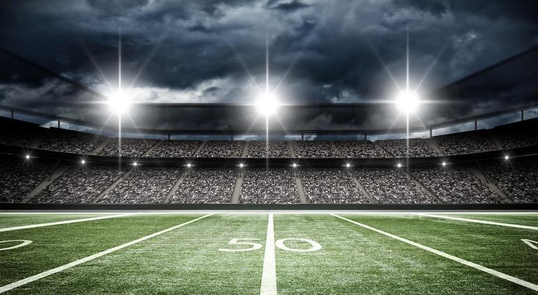 A football field under stadium lights