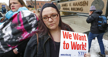 Woman holds sign 'we want to work'