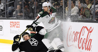 Marcus Foligno of the Wild against the boards with Oscar Fantenberg of the Kings