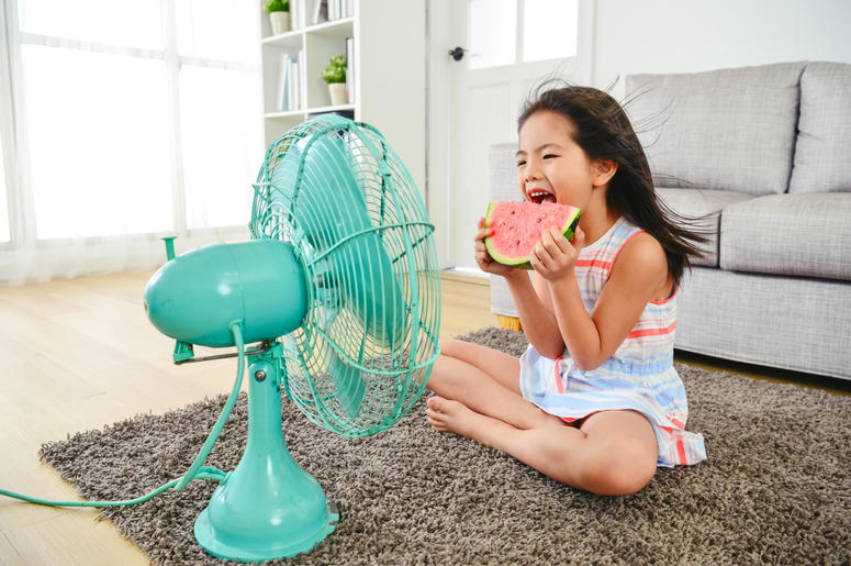 child eating watermelon with two hands. sitting in front of the electric fan