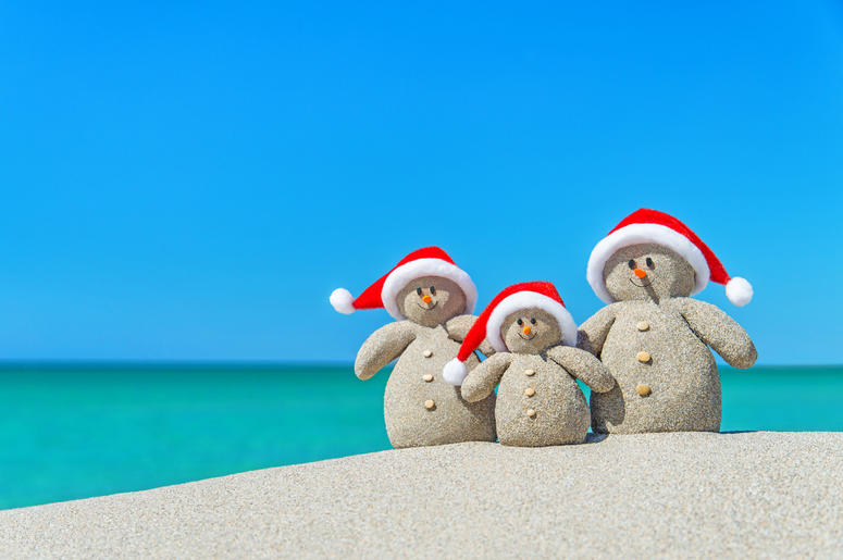 Christmas Snowmen in santa hats at tropical beach