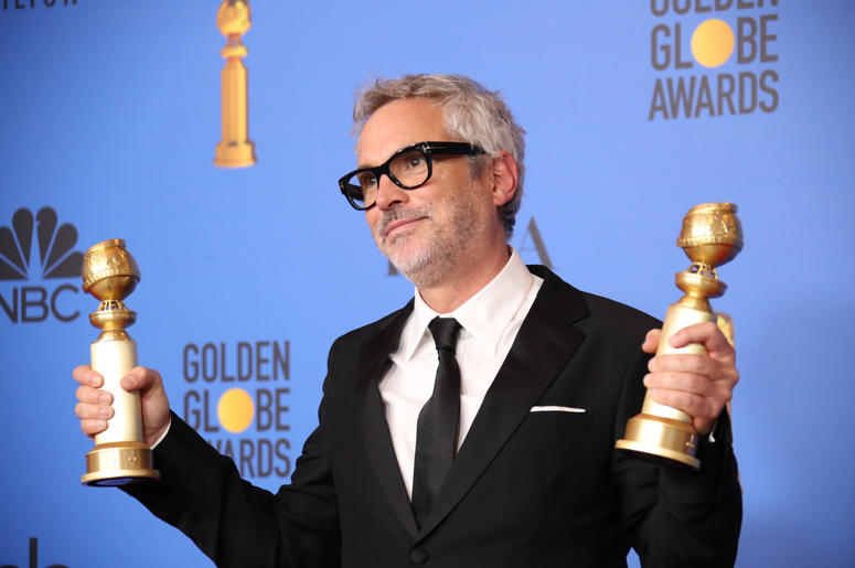 """Alfonso Cuaron poses in the press room with the awards for best director, motion picture and best motion picture, foreign language for \""""Roma\"""" at the 76th Golden Globe Awards at the Beverly Hilton."""
