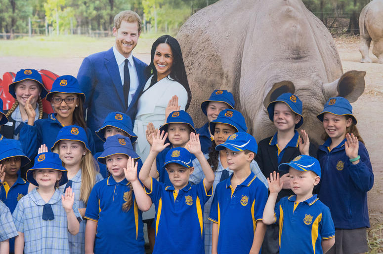 Pupils from South Dubbo Public School pose for a photo with a picture of the Duke and Duchess of Sussex as they await their arrival at Dubbo City Regional Airport, in Dubbo, New South Wales, on the second day of the royal couple's visit to Australia.