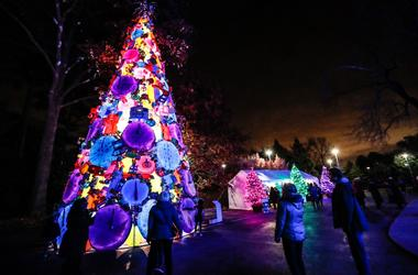 A giant Christmas tree made of plastic toys glows