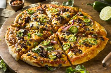 A whole pizza with sausage, olives and peppers