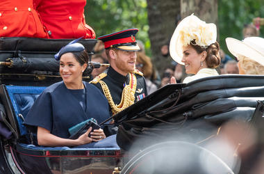Meghan, Duchess of Sussex rides in an open carriage with Prince Harry, Duke of Sussex and Catherine, Duchess of Cambridge