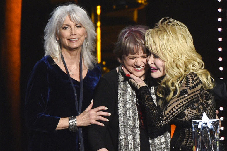 Emmylou Harris, from left, and Linda Ronstadt present Dolly Parton with the MusiCares Person of the Year award on Friday, Feb. 8, 2018