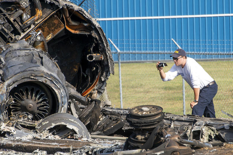 A member of the National Transportation Safety Board looks at the wreckage of a plane