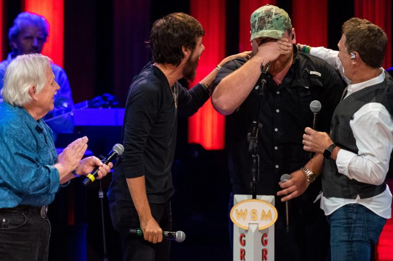 Luke Combs wipes his face after being surprised by John Conlee, Chris Janson and Craig Morgan, from left, with his invitation to the Grand Ole Opry at the Grand Ole Opr