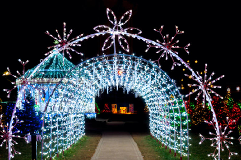 A tunnel of Christmas lights adds a bright note to a festive village outdoor display