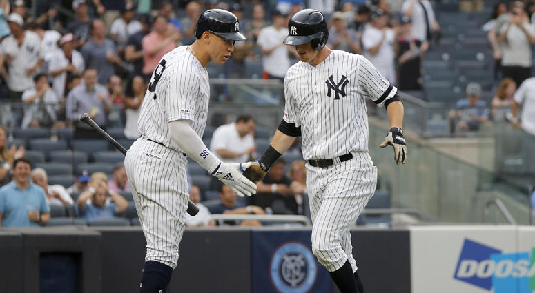 DJ LeMahieu of the New York Yankees celebrates his first-inning home run against the Toronto Blue Jays with teammate Aaron Judge at Yankee Stadium on June 25, 2019.