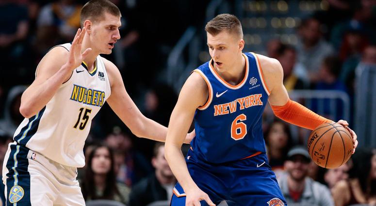 The Knicks' Kristaps Porzingis dribbles against the Nuggets' Nikola Jokic on Jan. 25, 2018 at the the Pepsi Center in Denver.