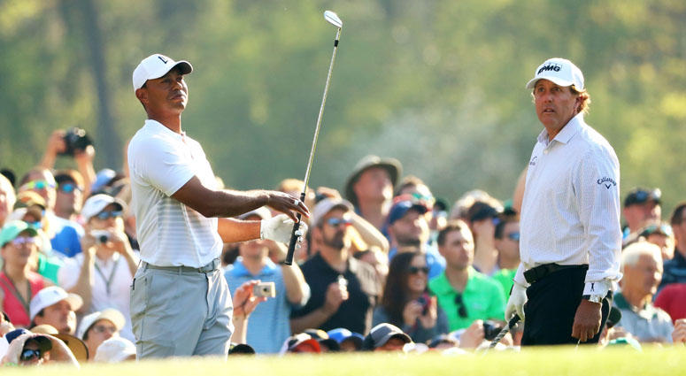 Phil Mickelson watches Tiger Woods play his tee shot on the 12th hole during a practice round for the Masters on April 3, 2018, at Augusta National.