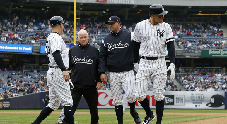 The Yankees' Aaron Judge is checked on by bench coach Josh Bard, trainer Steve Donohue and first-base coach Reggie Willits prior to leaving a game against the Kansas City Royals in the sixth inning at Yankee Stadium on April 20, 2019.