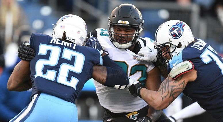 Titans running back Derrick Henry (22) is tackled for a loss by Jacksonville Jaguars defensive lineman Calais Campbell (93) on Dec. 31, 2017, at Nissan Stadium in Nashville.
